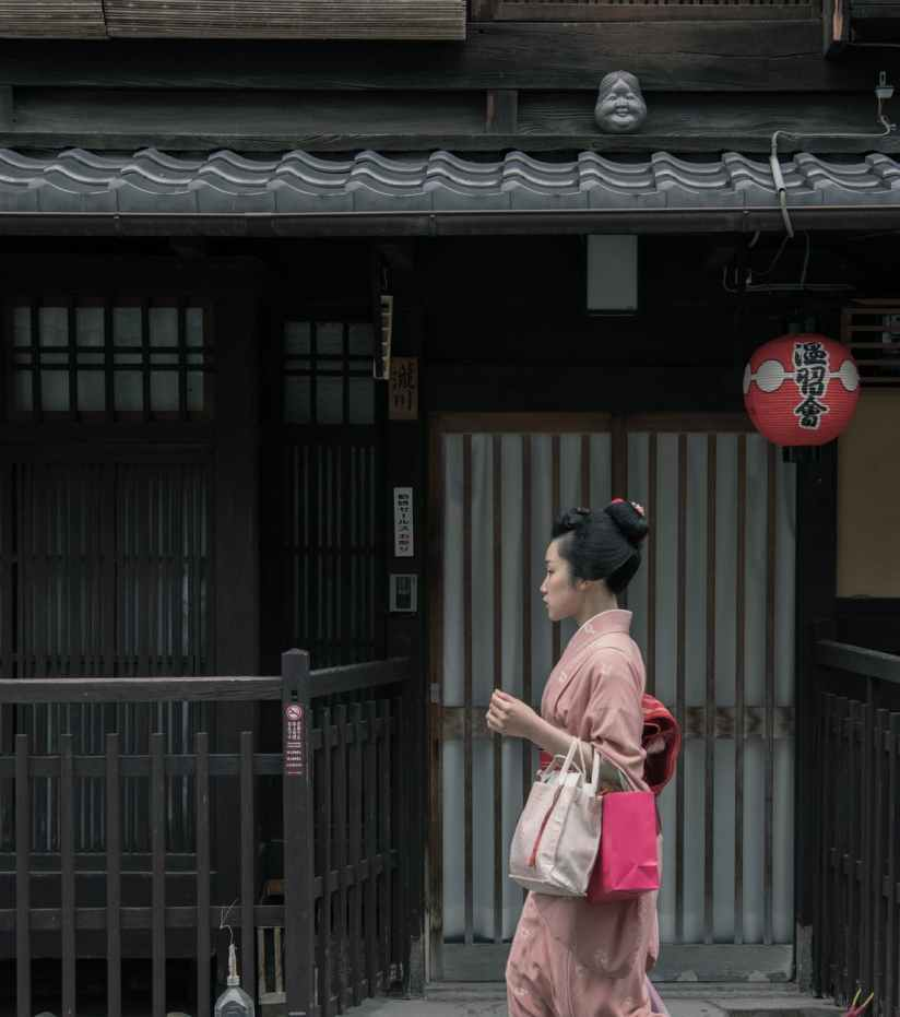 woman wearing pink kimono walking near houses