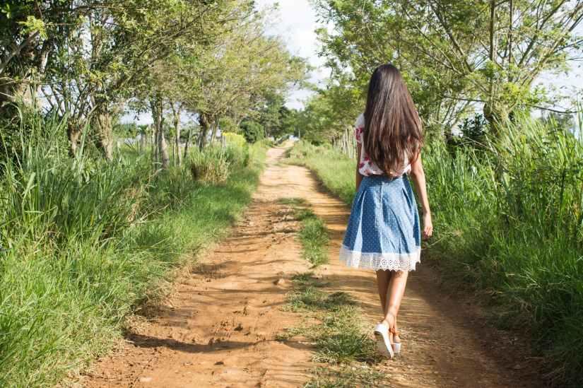 woman wearing blue and white skirt walking near green grass during daytime