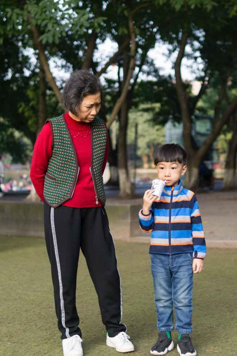 toddler boy standing beside woman