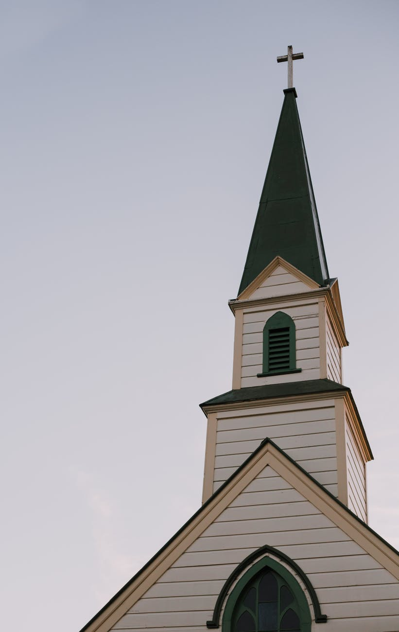 architectural photography of white and green church bell tower under clear sky
