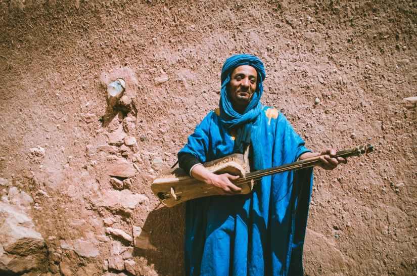 man wearing blue top holding brown string instrument
