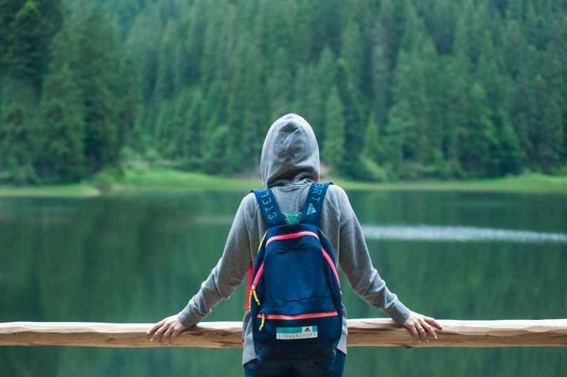 person wearing gray hoodie jacket watching lake