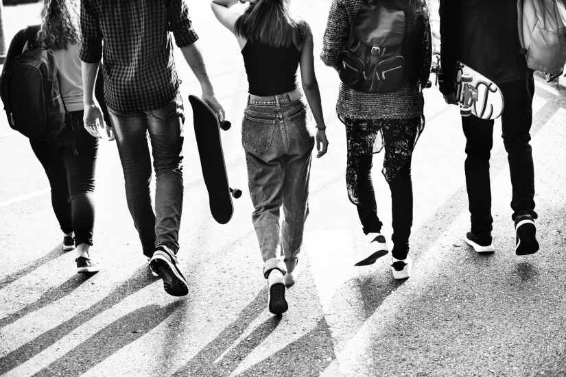 grayscale photography of five people walking on road