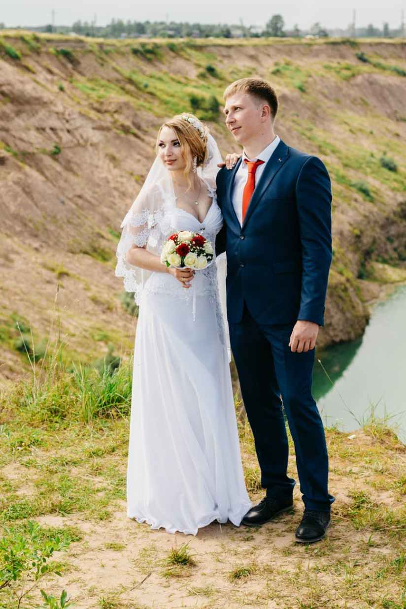 groom and bride standing near green grasses and river