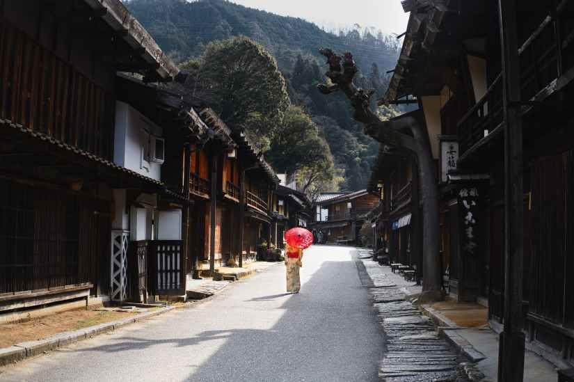 woman under umbrella walking through the street