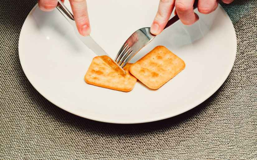 person slicing biscuit using stainless steel butter knife