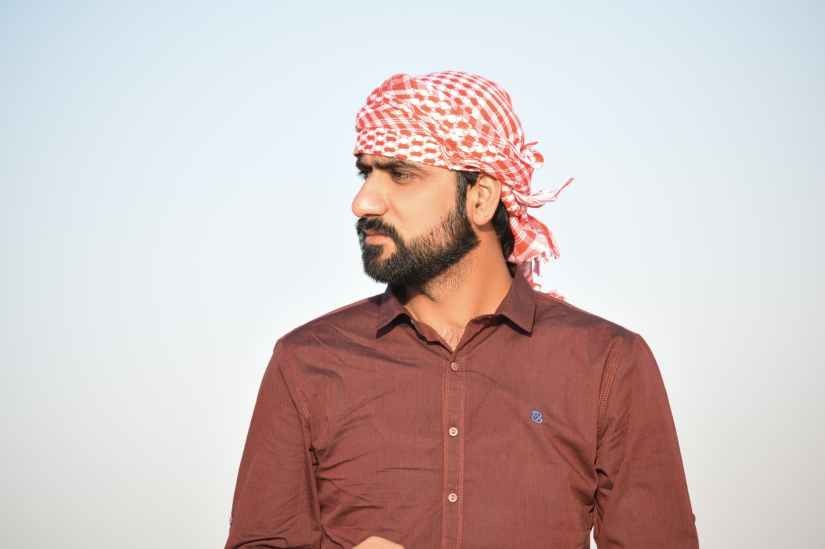 portrait photo of man in red button up shirt and red and white headscarf
