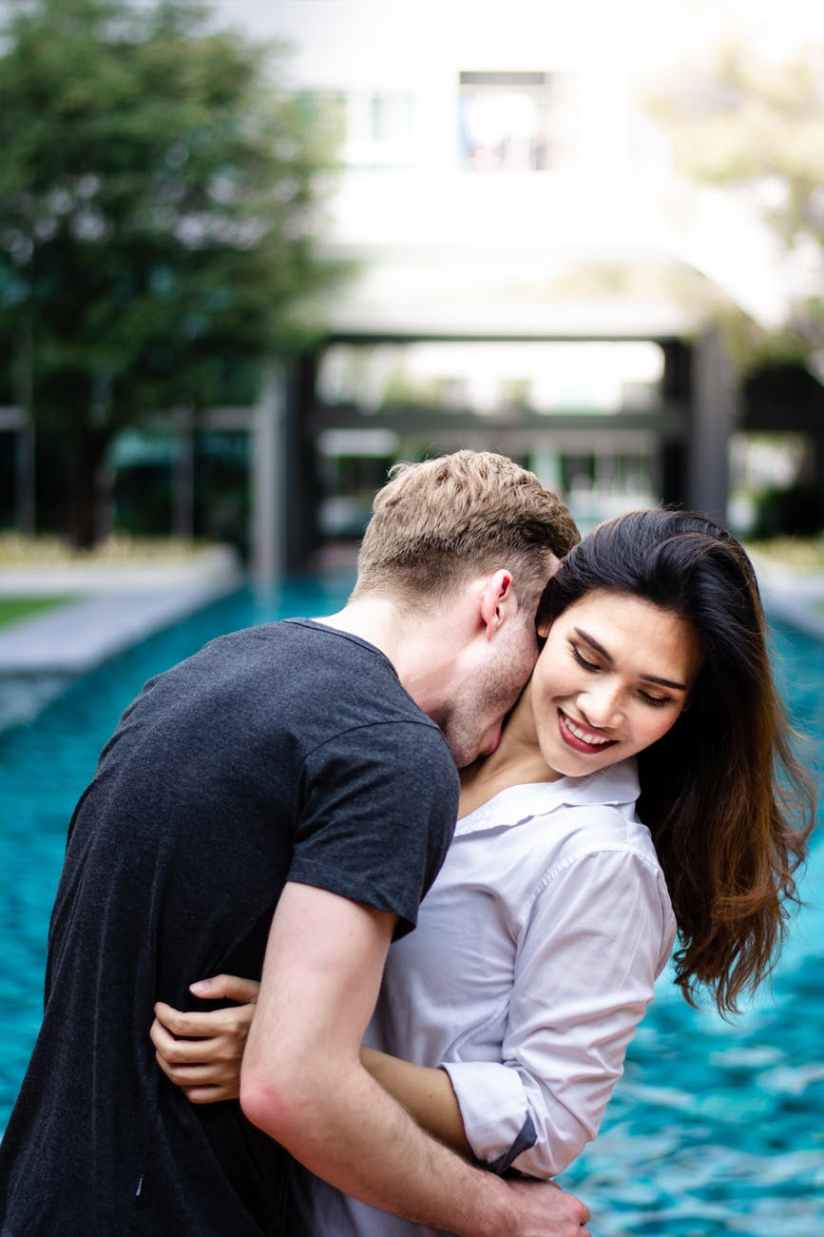 man kissing woman on neck near swimming pool