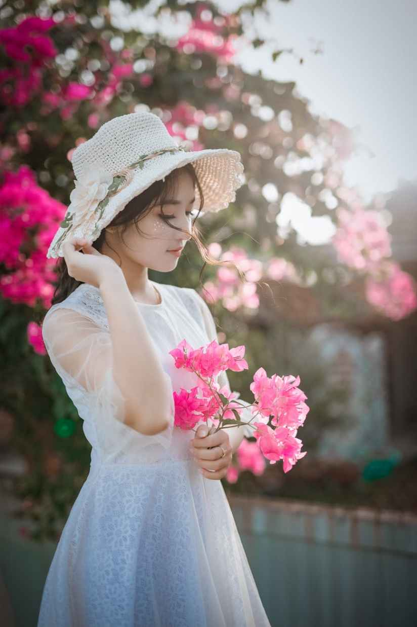 woman wearing sun hat and white dress holding pink bougainvilleas