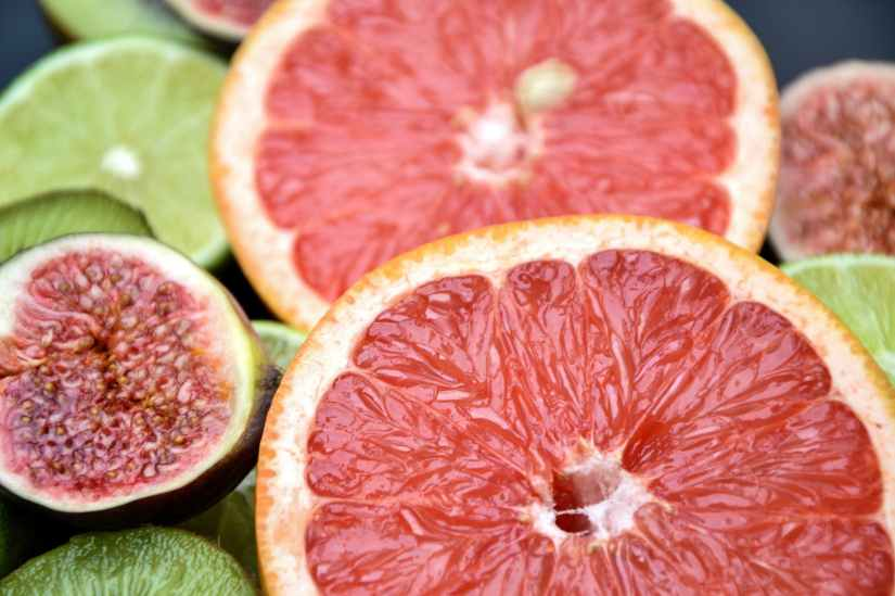 close up photo of grapefruits fig and limes