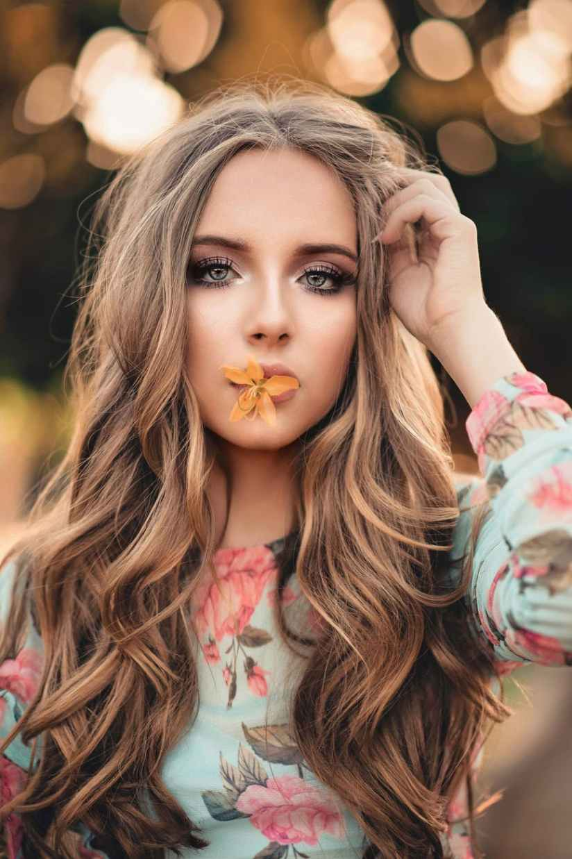 woman with orange petaled flower on her lips