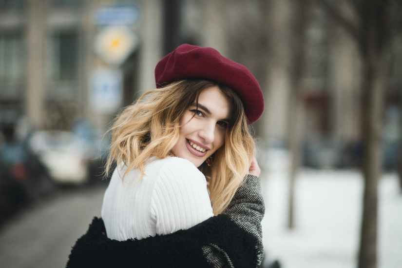 selective focus photography of smiling woman wearing red hat during snowy day