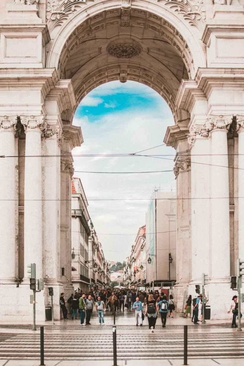 people walking under white concrete architecture