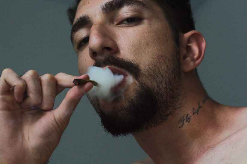 man smoking tobacco inside room