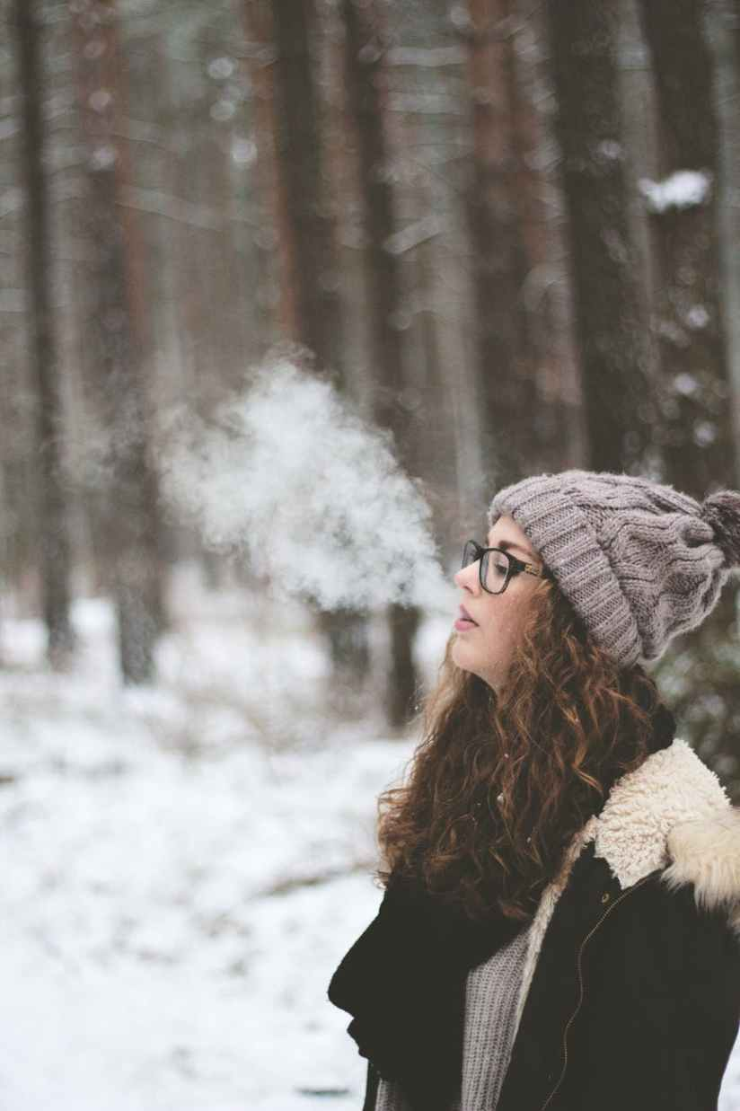 woman standing and smoking on snow covered forest