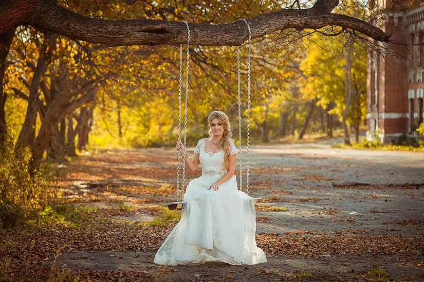 woman in white wedding gown sitting on swing hanging on tree