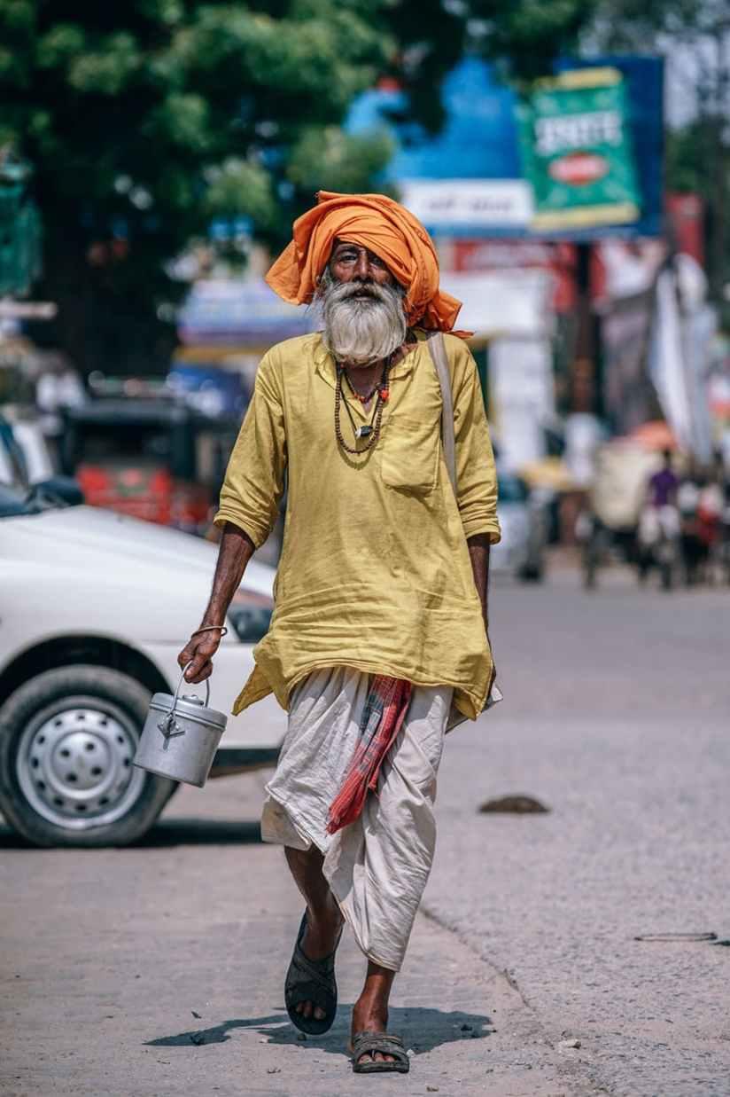 man walking on street carrying metal bucket