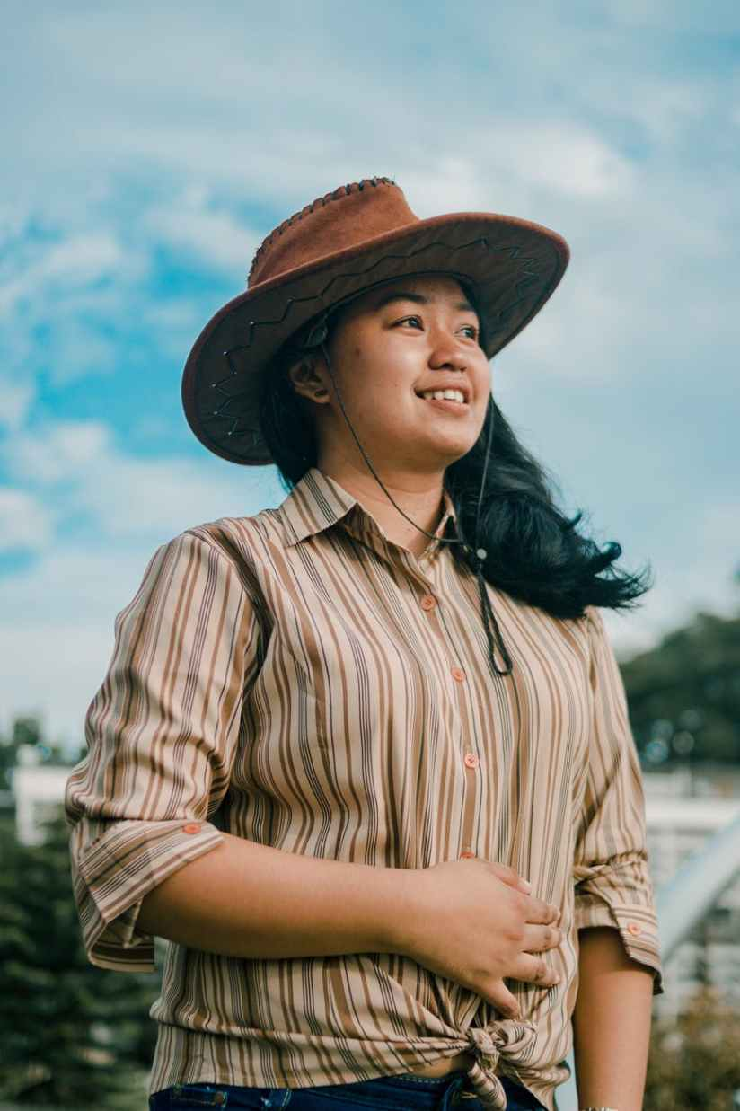 photograph of woman in brown striped shirt and hat
