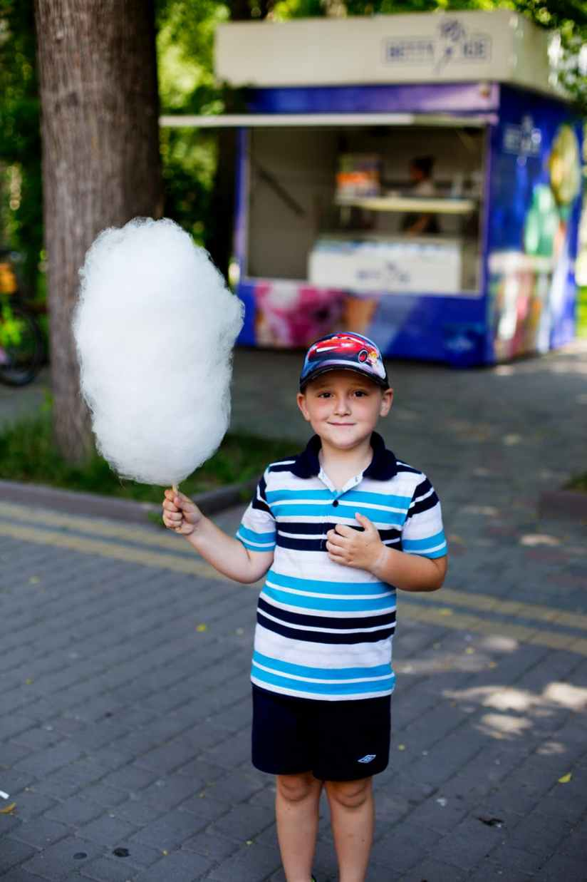 boy holding cotton candy at the park